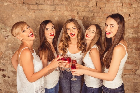 46389874 - beautiful bride with happy bridesmaids celebrating hen-party with red champagne